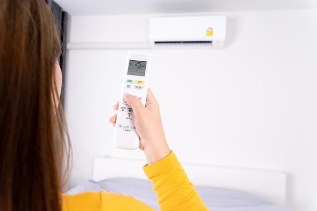 Frau mit weißer fernbedienung zum einstellen der temperatur der klimaanlage.