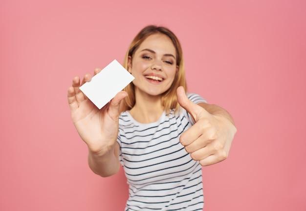 Frau mit weißer karte auf rosa hintergrund gestikuliert mit den händen beschnittene ansicht