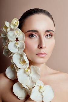 Frau mit weißer orchidee nahe gesichtsmädchenmake-up