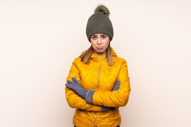 Frau mit winterhut über der lokalisierten wand traurig
