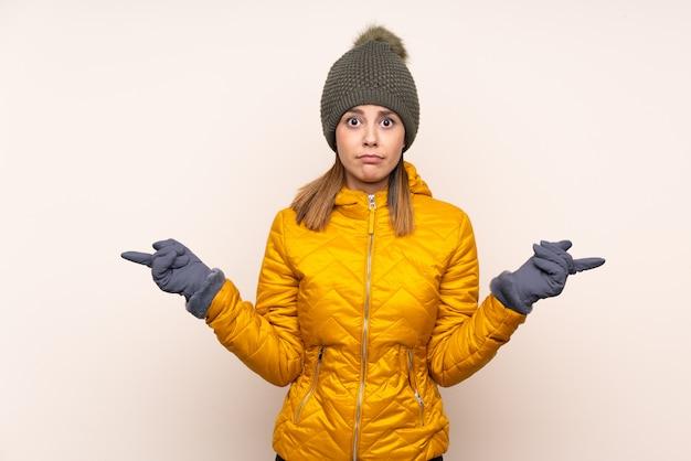 Frau mit winterhut über wand zeigend auf die seitenteile, die zweifel haben