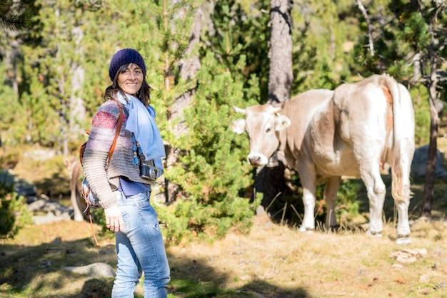 Frau mit wollmütze, die im wald mit einer kamera um ihren hals mit einer kuh steht