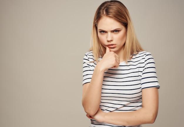 Frau mit wütendem gesichtsausdruck gestreiftes t-shirt emotionen studio. foto in hoher qualität