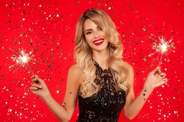 Frau mit wunderkerze neujahrsparty feiern. porträt des schönen lächelnden mädchens in glänzendem schwarzem kleiderwerfendem konfetti