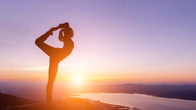 Frau mit yoga-haltung auf dem berg bei sonnenuntergang