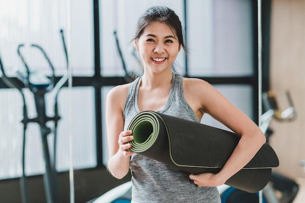 Frau mit yoga-matte im fitness-studio