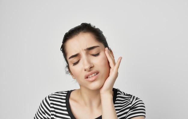 Frau mit zahnschmerzen, die gesichtsgesundheitsprobleme unzufriedenheit in der zahnmedizin hält