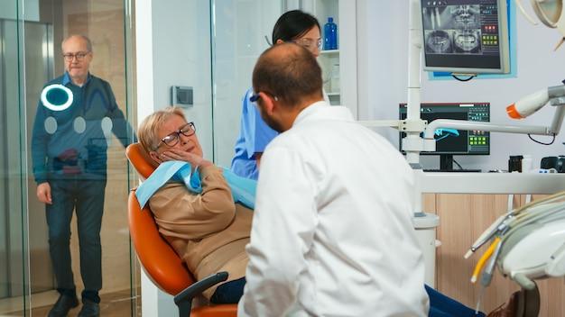 Frau mit zahnschmerzen, die mit kieferorthopädie spricht und betroffene masse zeigt. älterer patient, der dem arzt ein zahnproblem erklärt, während er in einer modernen privatklinik vor dem eingriff auf dem stomatologen sitzt