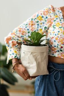 Frau mit zimmerpflanze in umweltfreundlicher papiertüte