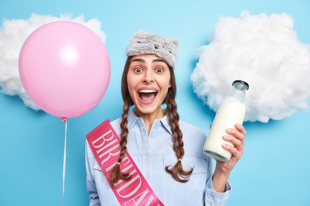 Frau mit zöpfen hält den mund offen reagiert auf erstaunliche neuigkeiten hält eine flasche frischer milch aufgeblasener ballon trägt schlafmaske auf der stirn hemd mit band geschrieben geburtstag auf