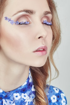Frau mit zöpfen und blauen blumen auf wimpern