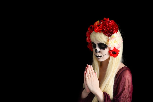 Frau mit zuckerschädel-make-up und blondem haar lokalisiert auf schwarz.