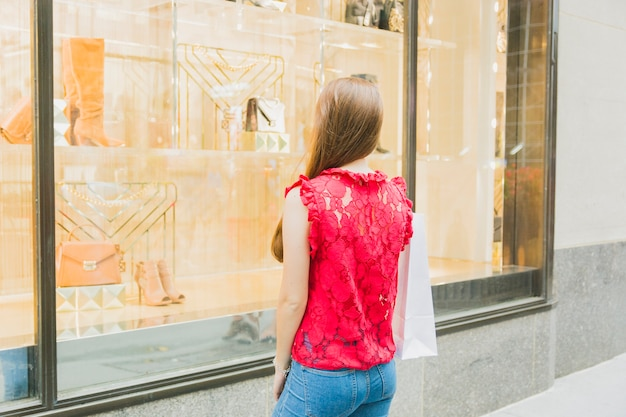 Frau mit zurück nahem einkaufsfenster des einkaufens