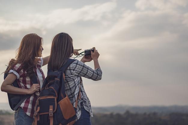 Frau mit zwei touristen, die ein foto mit kamera in der natur macht