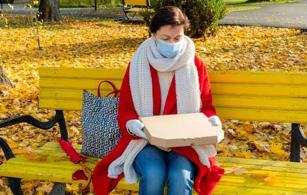 Frau mittleren alters 50 plus mit schützender medizinischer maske, die auf einer gelben bank im herbstpark mit kasten für pizza sitzt.