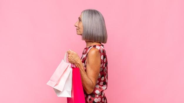 Frau mittleren alters auf profilansicht, die raum voraus kopiert, denkt, sich vorstellt oder mit einkaufstüten träumt
