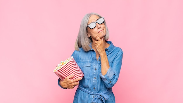 Frau mittleren alters denkt, fühlt sich zweifelhaft und verwirrt, hat verschiedene möglichkeiten und fragt sich, welche entscheidung sie für ein filmkonzept treffen soll