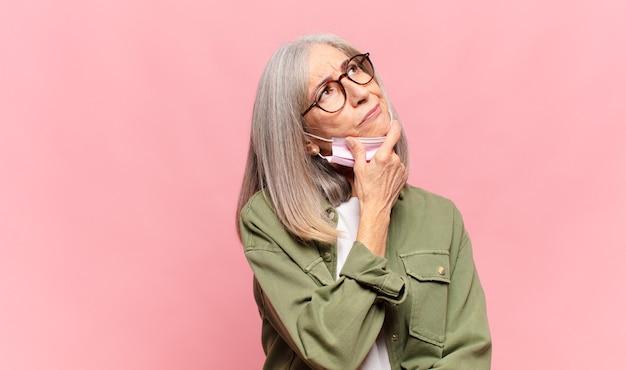 Frau mittleren alters denkt, fühlt sich zweifelhaft und verwirrt, hat verschiedene möglichkeiten und fragt sich, welche entscheidung sie treffen soll