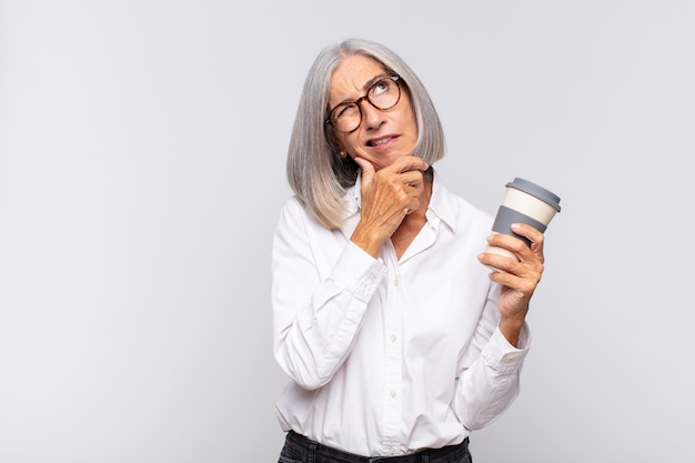 Frau mittleren alters denkt, fühlt sich zweifelhaft und verwirrt, mit verschiedenen möglichkeiten