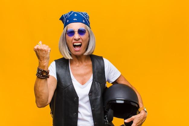 Frau mittleren alters, die aggressiv mit einem wütenden ausdruck oder mit geballten fäusten schreit, um erfolg zu feiern