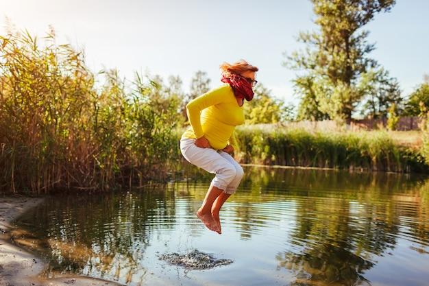 Frau mittleren alters, die am herbsttag am ufer des flusses springt. glückliche ältere dame, die spaß beim wandern im wald hat. sich energiegeladen und frei fühlen