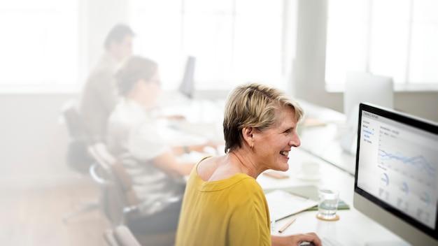Frau mittleren alters, die an einem computer arbeitet