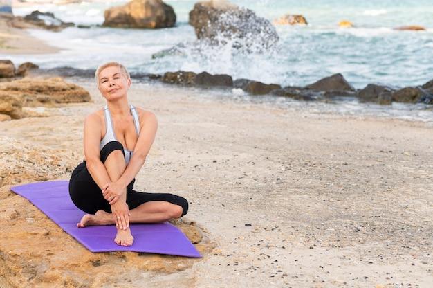 Frau mittleren alters, die an einem strand sitzt und yogaübung macht