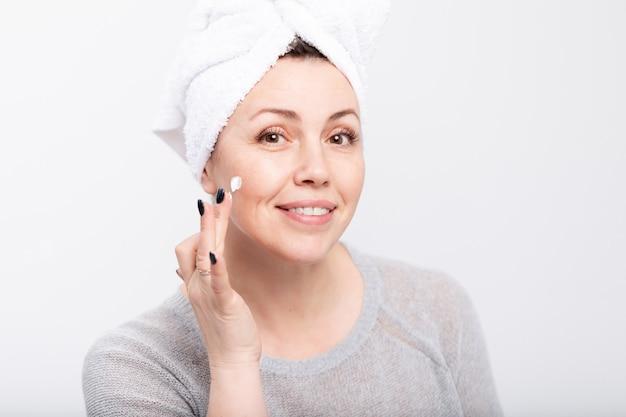 Frau mittleren alters, die anti-aging-creme vor dem spiegel aufträgt