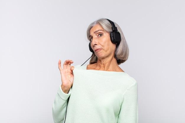Frau mittleren alters, die arrogant, erfolgreich, positiv und stolz aussieht und auf sich selbst zeigt. musikkonzept