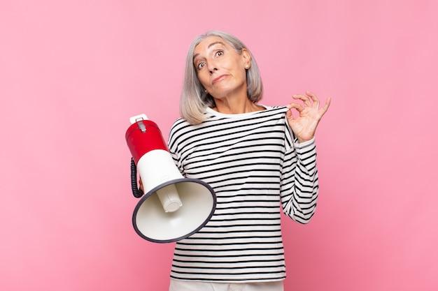 Frau mittleren alters, die arrogant, erfolgreich, positiv und stolz aussieht und mit einem megaphon auf sich selbst zeigt