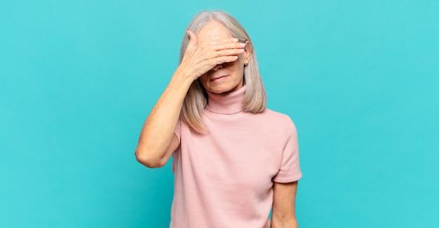 Frau mittleren alters, die augen mit einer hand bedeckt, die sich ängstlich oder ängstlich fühlt, sich wundert oder blind auf eine überraschung wartet