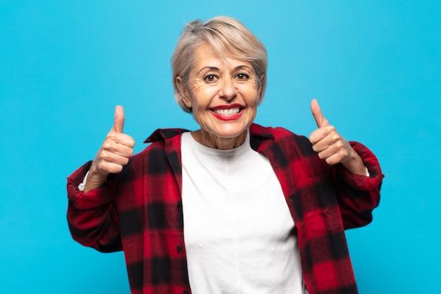 Frau mittleren alters, die breit lächelnd glücklich, positiv, selbstbewusst und erfolgreich aussieht, mit beiden daumen nach oben