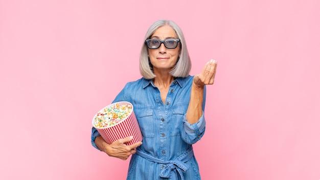 Frau mittleren alters, die capice oder geldgeste macht und ihnen sagt, sie sollen ihre schulden bezahlen! filmkonzept