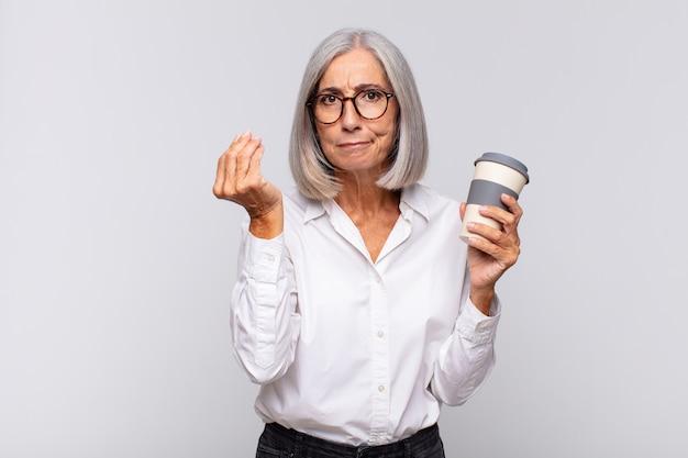 Frau mittleren alters, die capice oder geldgeste macht und ihnen sagt, sie sollen ihre schulden bezahlen! kaffeekonzept