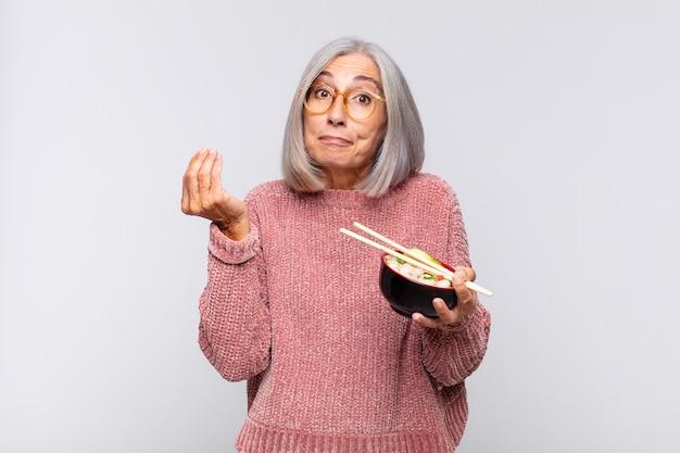 Frau mittleren alters, die capice oder geldgeste macht und ihnen sagt, sie sollen ihre schulden bezahlen!