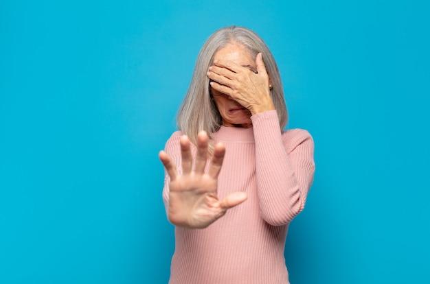 Frau mittleren alters, die das gesicht mit der hand bedeckt und die andere hand nach vorne legt, um anzuhalten und fotos oder bilder abzulehnen