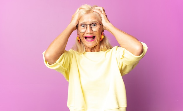 Frau mittleren alters, die die hände zum kopf hebt, mit offenem mund, extrem glücklich, überrascht, aufgeregt und glücklich