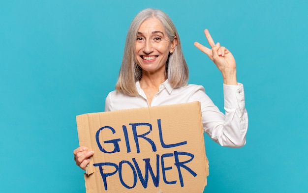 Frau mittleren alters, die ein zeichen mit dem text mädchenkraft hält