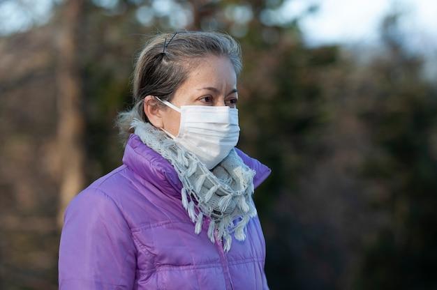 Frau mittleren alters, die eine weiße chirurgische maske zum schutz gegen coronavirus trägt