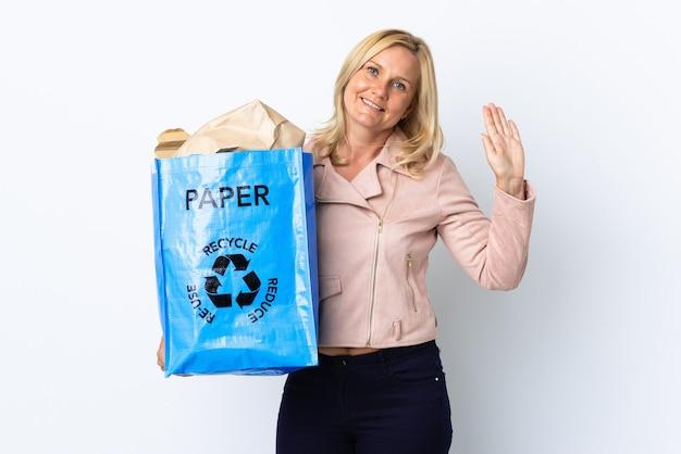 Frau mittleren alters, die einen recyclingbeutel voll papier hält, um lokalisiert auf weißem gruß mit hand mit glücklichem ausdruck zu recyceln
