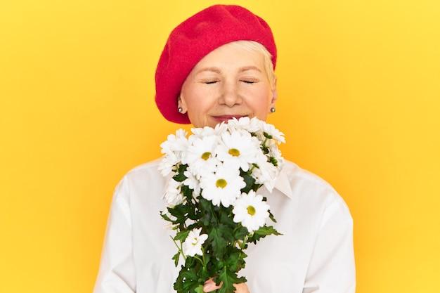 Frau mittleren alters, die elegante rote haube hält, die blumenstrauß der weißen löwenzahnblumen hält, die an ihrem geburtstag gegeben werden, glücklichen freudigen blick haben, augen mit vergnügen schließen, frischen blumenduft einatmen