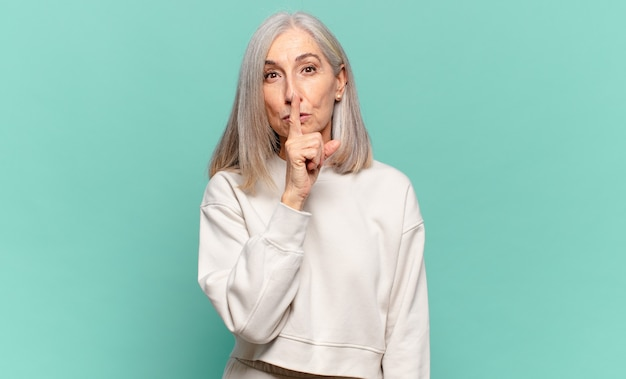 Frau mittleren alters, die ernst aussieht und mit dem finger auf die lippen drückt, die stille oder ruhe fordern und ein geheimnis bewahren