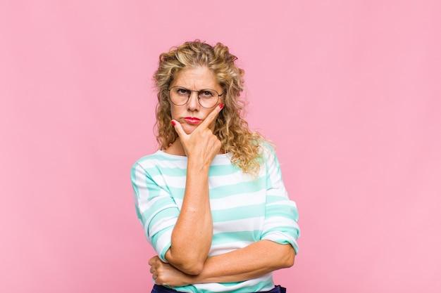 Frau mittleren alters, die ernst, nachdenklich und misstrauisch aussieht, mit einem arm verschränkt und hand am kinn, gewichtungsoptionen