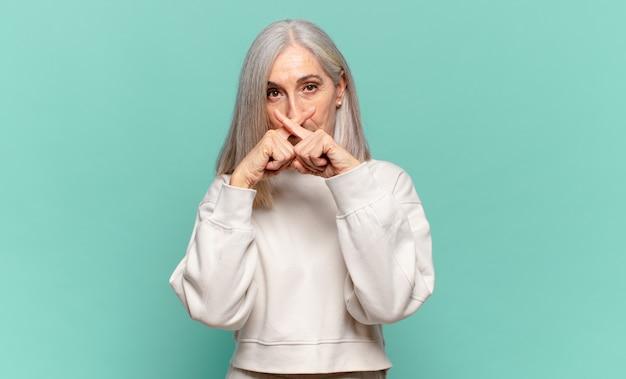 Frau mittleren alters, die ernst und unzufrieden aussieht, wobei beide finger vor ablehnung gekreuzt sind und um stille bitten