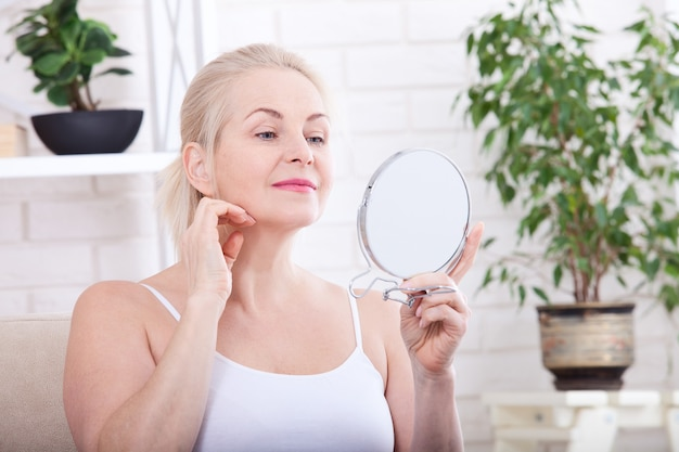 Frau mittleren alters, die falten im spiegel betrachtet. selektiver fokus