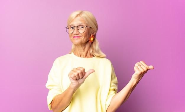 Frau mittleren alters, die fröhlich lächelt und beiläufig zeigt, um platz auf der seite zu kopieren, sich glücklich und zufrieden fühlend