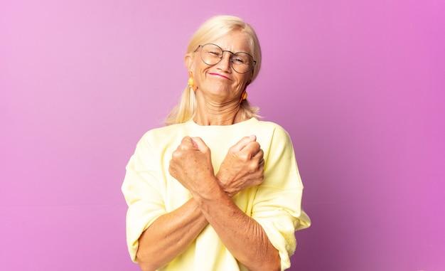 Frau mittleren alters, die fröhlich lächelt und feiert, mit geballten fäusten und verschränkten armen, die sich glücklich und positiv fühlen