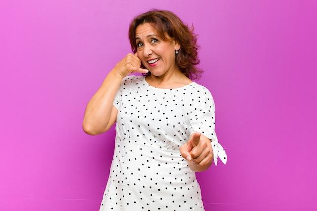 Frau mittleren alters, die fröhlich lächelt und zur kamera zeigt, während sie einen anruf tätigen, den sie später gestikulieren und am telefon gegen lila wand sprechen