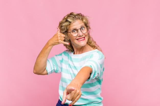 Frau mittleren alters, die fröhlich lächelt und zur kamera zeigt, während sie einen anruf tätigen, den sie später gestikulieren und am telefon sprechen