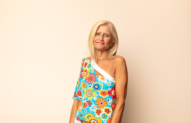 Frau mittleren alters, die fröhlich und lässig mit einem positiven, glücklichen, selbstbewussten und entspannten ausdruck lächelt